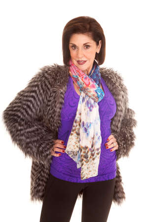 An older woman in her purple top and fur coat with a small smile on her lips Stock Photo