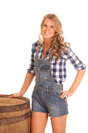 tomboy: A cowgirl in her plaid shirt and overalls by a barrel. Stock Photo