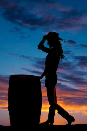A silhouette of a cowgirl standing in the outdoors by a barrel. photo