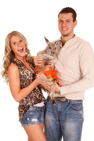 A couple with big smiles on their faces holding on to their pet kangaroo. photo