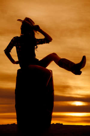 A silhouette of a woman sitting on a barrel in her cowgirl hat and boots. Stock Photo