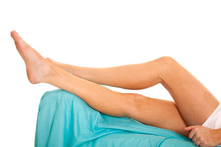 A woman with her legs up on a blue bed. photo