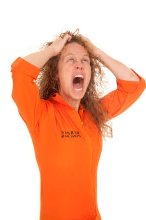 an inmate: A woman in her orange inmate uniform pulling her hair out.