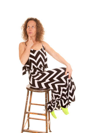 An older woman sitting on a stool with her finger up to her mouth, with a funny expression.