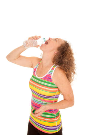 A woman in her colorful fitness tank drinking her water bottle.