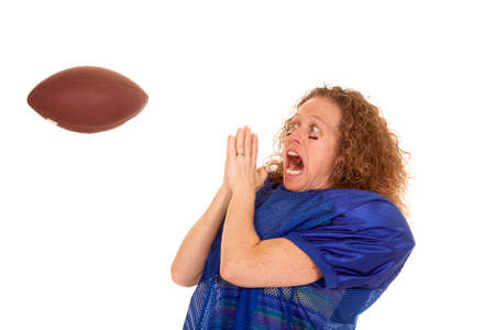 a woman in her football uniform scared with a football coming at her face. photo