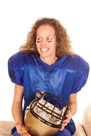 A woman in her football pads sitting while holding on to a helmet.