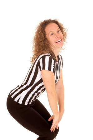bending over: A woman referee bending over looking and smiling.