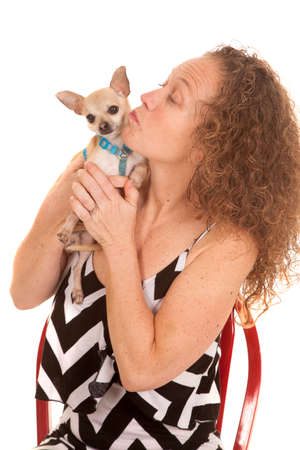 stitting: A woman in her dress stitting and loving on her little puppy. Stock Photo