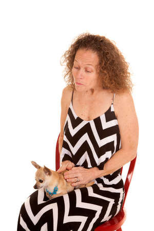 A woman in her dress sitting down holding on and loving her puppy.