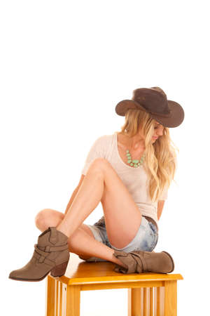 a cowgirl in her hat and boots sitting on a wooden table looking down. Stock Photo