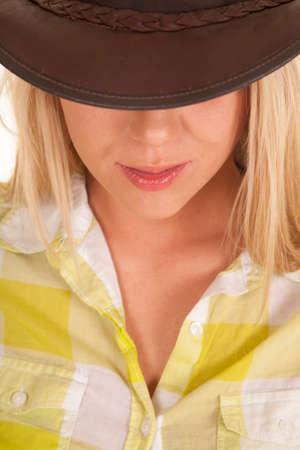 cowgirl hat: Un primer plano de una mujer en su sombrero de vaquera con los ojos ocultos.