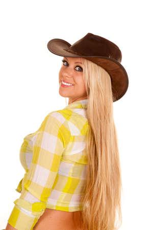 cowgirl hat: una mujer en su sombrero de vaquera mirando sobre su hombro.