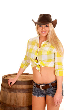 a woman with a smile on her face in her cowgirl hat and short shorts.