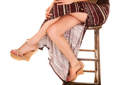 A close up of a woman sitting on a stool showing her legs.  photo