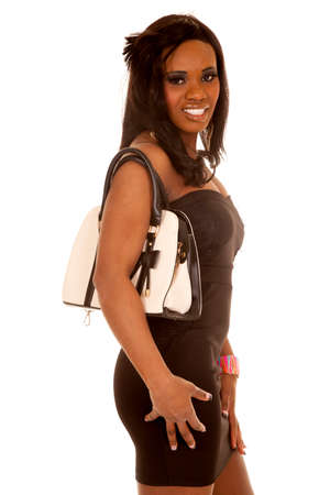 An African American woman standing carrying a purse on her shoulder.