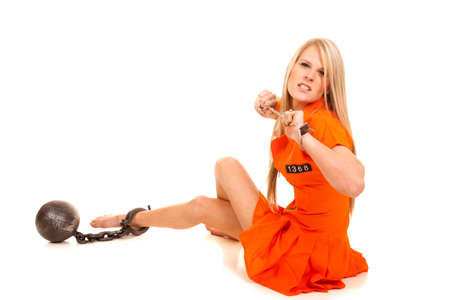 A woman in her orange jump suit trying to get out of her hand cuffs. photo