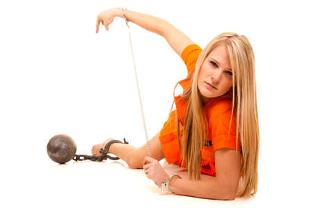 A woman laying on her side with a ball and chain locked to her foot and her handcuffs on. photo