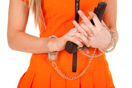 a close up of a woman holding on to a gun with hand cuffs on Stock Photo - 28112803