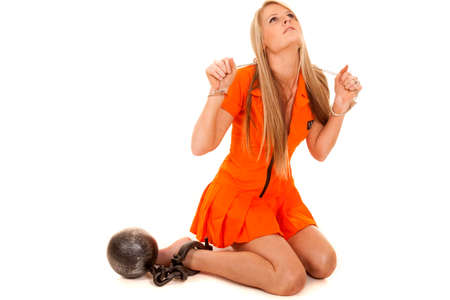 A woman in her prisoner outfit with handcuffs and a ball chain. Stock Photo - 28074317