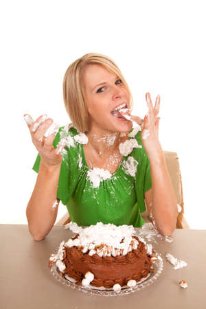 A woman licking her fingers after touching the cake. photo