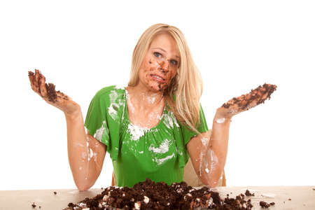A woman with her hands up and cake all over her face, body and hands. photo