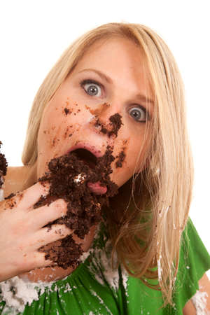a woman with wide eyes shoving her face with chocolate cake. photo