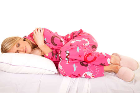 A woman with her eyes closed in her pajamas. Imagens