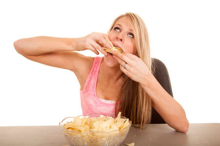 A woman shoving her face with potato chips. Imagens