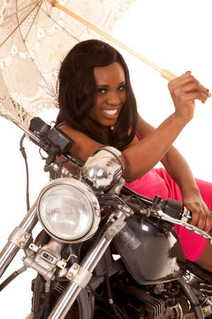 an African American laying on her motorcycle in her pink dress, and umbrella. 免版税图像
