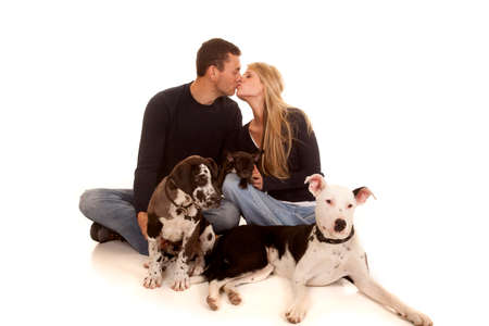 A couple sitting on the ground kissing with their dogs. photo