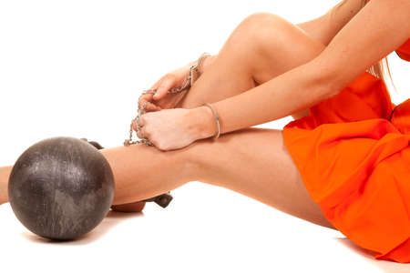 A close up of a womans legs in her orange jumpsuit with hand cuffs and a ball and chain. photo