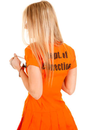 cuffs: A woman in her orange jumpsuit with  handcuffs on . Stock Photo