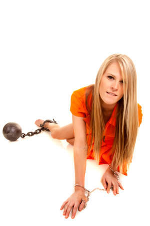 a woman in her orange jumpsuit crawling forward with a chain on her leg. Stock Photo - 28074390