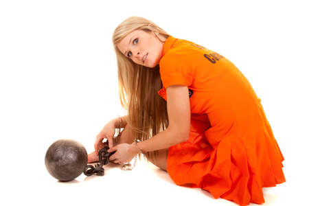 A woman sitting in her orange jumpsuit with her ball and chain on her foot. Banco de Imagens