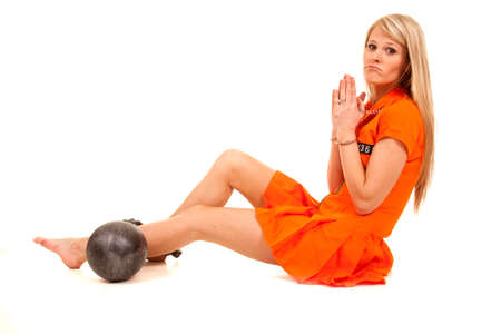 a woman in her orange jumpsuit trying to pray her way out of jail. Stock Photo - 28074393