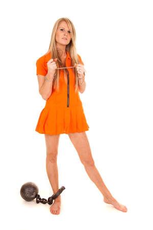 eine Frau gefangen in ihrem orangefarbenen Overall hält ihre Handschellen.