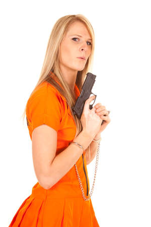 a prisoner in her orange jumpsuit blowing on the tip of a gun.
