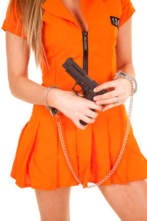 a woman in her orange jump suit with her gun, and hand cuffs on.