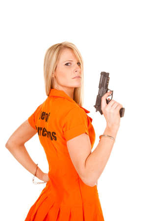 A woman in her prisoner outfit on holding on to a pistol. photo