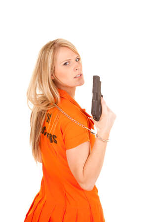 A woman in her prisoner outfit looking over her shoulder, holding on to a gun. Stock Photo - 28112635