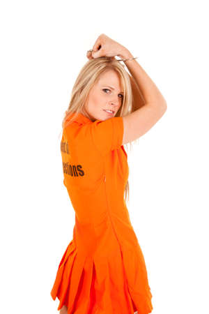 a woman in her orange jumpsuit holding up her handcuffs, photo