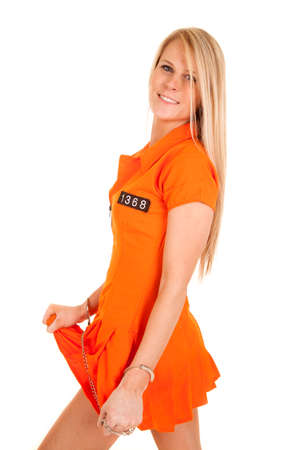 A woman in her orange jumpsuit pulling on her skirt. photo