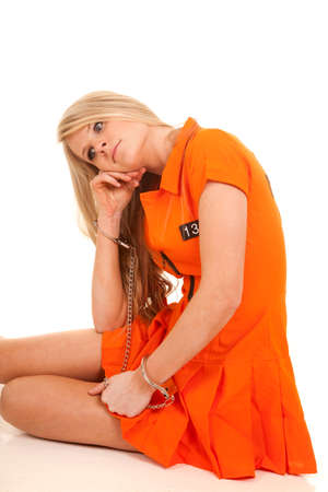A woman in her orange jumpsuit sitting with her hand cuffs on. Stock Photo - 28112637