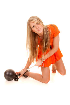 A woman kneeling in her orange jumpsuit trying to get her ball and chain off of her foot.