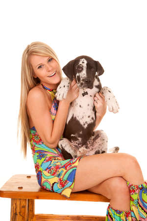 a woman in her hippie clothing sitting on a bench holding on to her dog. Stock Photo