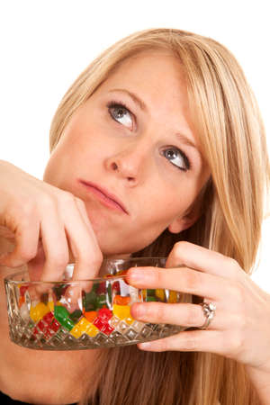 A woman with a bowl full of jelly beans, reaching in a and eating them. photo