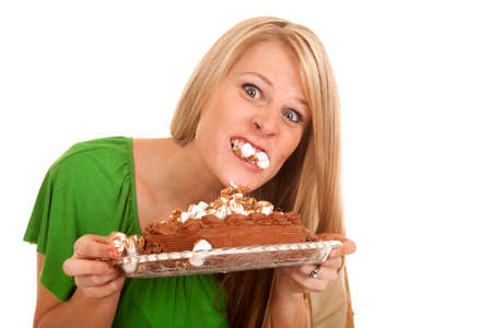 A woman taking a bite of the top of the cake . photo