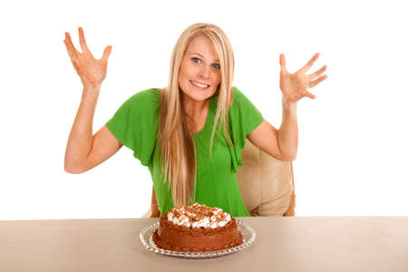 A woman with a cake on the table with her hands out and a smile on her lips. photo