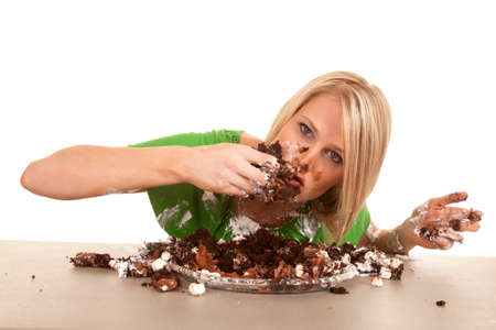 messy: A woman leaning over her chocolate cake, shoving her face.